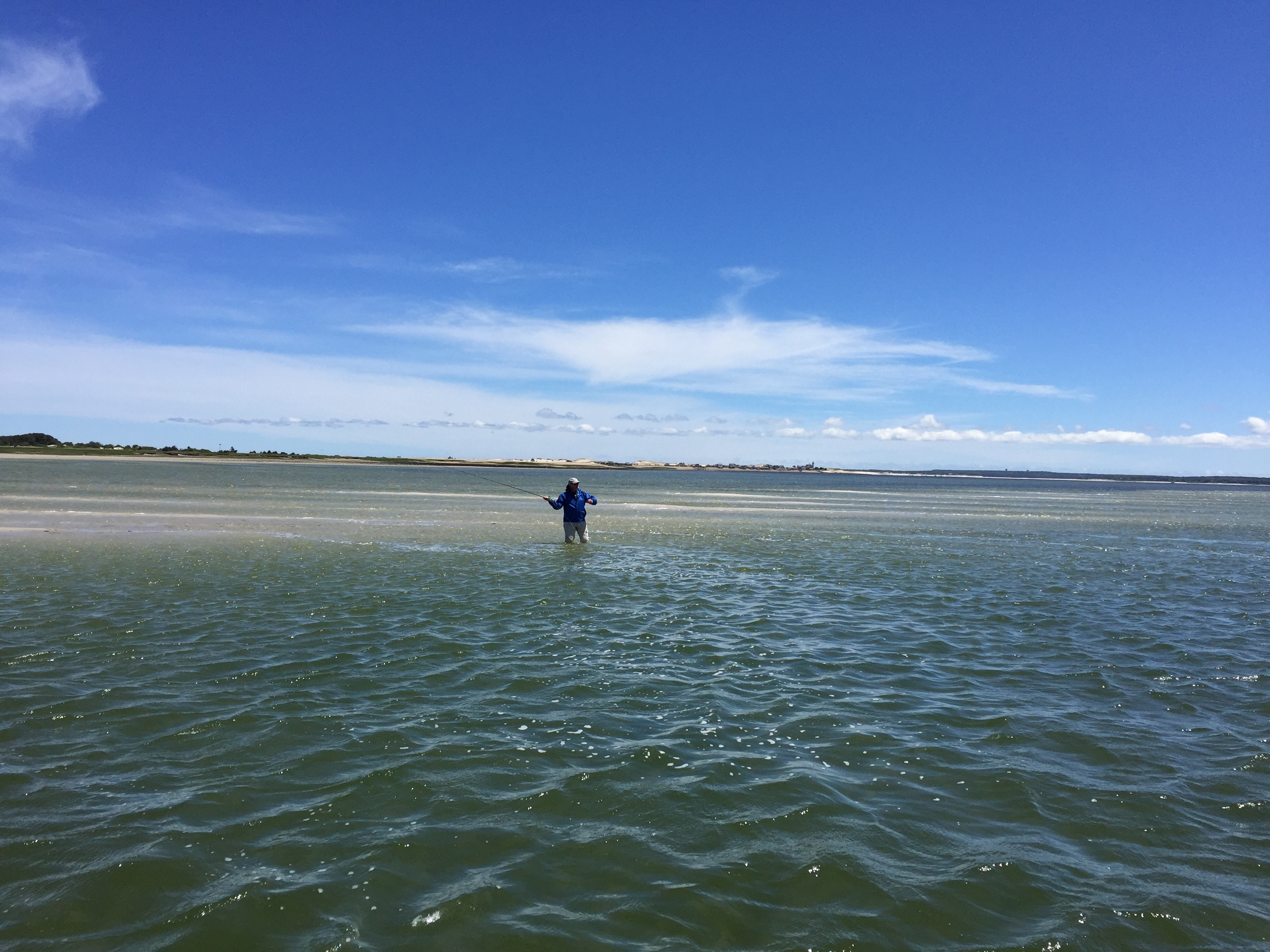 Man on a sand flat fly fishing